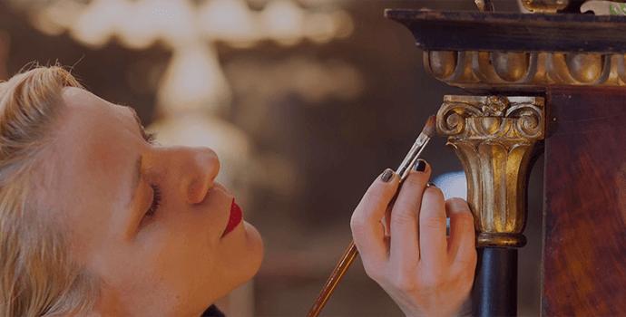 Woman restoring art piece with brush